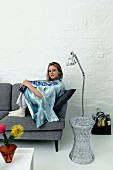 Young woman sitting on grey, retro sofa, transparent side table and stainless steel standard lamp