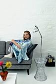 Junge Frau auf grauem Retro Sofa, transparenter Beistelltisch und Edelstahl Stehleuchte