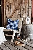 Sessel mit Kissen auf rustikalem Dielenboden vor Holzwand auf Veranda
