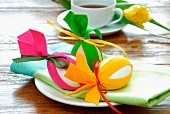 Easter decorations - eggs decorated with strips of colourful felt and linen napkin on plate