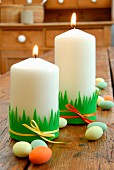 Easter decorations - pillar candles decorated with strips of felt on rustic wooden table