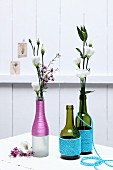 Various bottled wrapped in colourful cord and used as vases