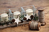 Hand-crafted tealight holders with Advent arrangement of pine cones and white wooden stars in long wooden tray