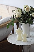 Angel candles in front of jug of dried white roses on vintage metal table
