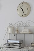 Clock above crockery and kitchen scales on vintage shelves