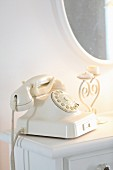 Vintage telephone and candlestick on white table