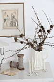 Larch branches with small cones in china jug, flower-shaped candle holders and vintage reels of twine on console table
