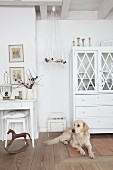 Advent wreath suspended between white console table and dresser in shabby-chic interior with golden retriever in foreground