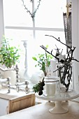 Christmas arrangement on china cake stand; candlesticks and potted plants on windowsill in background