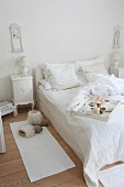 Breakfast tray on bed in vintage-style white shabby-chic bedroom