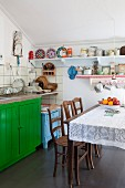 Dining table with lace tablecloth and antique chairs in front of sink on green-painted based unit in simple kitchen