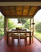 Modern dining set on red-painted floor; pale wooden chairs and table in room with glass walls and view of garden