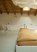 Bed with ochre bed linen and free-standing, modern bathtub in open-plan attic room with wooden ceiling