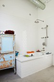 Bathtub and vintage cupboard with peeling paint in bathroom with white wall tiles