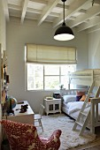 White flokati rug next to bunk beds in children's bedroom with white wooden ceiling and patterned armchair in foreground