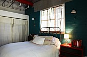 Bed with vintage metal frame below window and table lamp on red bedside cabinet against brick wall painted dark green