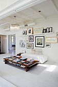 Stacks of books on low coffee table, simple couch with white cover on whitewashed brick floor and gallery of pictures on wall