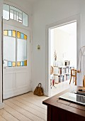 Art-nouveau-style door with stained-glass panels, view into dining room with books on sideboard