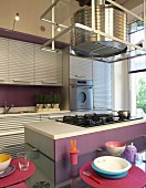 Kitchen with corrugated metal fronts and futuristic extractor hood above hob on island counter with integrated dining table