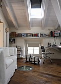 White sofa and desk in attic with exposed, white-painted roof structure