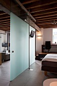 Glass partition with sliding door between bedroom and living areas in elegant loft apartment with rustic, wood-beamed ceiling