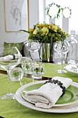 Festively set table - linen napkin on green plate and matching runners