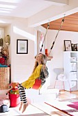 Girl on swing in open-plan interior, toys on floor and retro chair and shelving next to open doorway