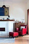 Red leather armchair with matching footstool next to open fireplace in corner of traditional room