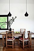 Designer pendant lamp with black lampshade (Tom Dixon) above rustic wooden chairs and table