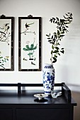 White and blue painted porcelain vase on black sideboard below framed pictures with Oriental motifs