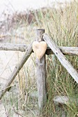 Wooden heart hanging on fence on beach