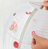 Embellishing a paper lantern with stick-on flower motifs