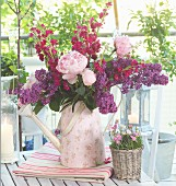 Bouquet of garden flowers with peonies, stocks and lilac in retro watering can with floral pattern