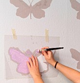 Hand-crafted butterfly stencil used as template for painting pattern on wall - woman's hands holding paintbrush