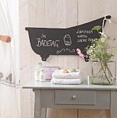 Hand-crafted, bathtub-shaped blackboard on white, wooden bathroom wall