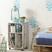 Upcycled cabinet made from wine crate on castors with hurricane lamp on top against wall with light blue stencilled pattern