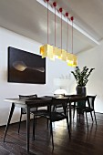 Designer dining table with retro character and matching black chairs below row of pendant lamps with pale yellow, paper lampshades