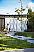 Children playing in sandpit in front of garage with steel and plexiglas sliding doors with zigzag patterns in summery garden