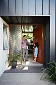 Vater und Tochter im überdachten Eingangsbereich eines Wohnhauses mit grauschwarzer Metallfassade; neben der offenen Tür ein verglastes Element mit Zickzack-Struktur