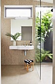 Sink on bathroom wall covered in round, beige iridescent mosaic tiles; walk-in shower with glass wall looking into planted courtyard