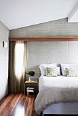 Double bed with structured bedspread against soft textures of pale grey brick wall and parquet floor made of spotted gum wood native to Australia
