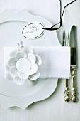 Weisses Gedeck mit Porzellanblüte und beschriftetem Anhänger 'bon appétit'