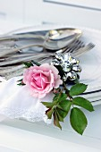 Silberbesteck, Serviettenhalter, Rose & Stoffserviette auf Tellerstapel