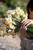 Boy holding bouquet of narcissus in garden
