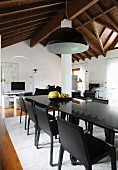Black dining set under black and white pendant lamp in modern, open-plan interior with rustic wood-beamed ceiling