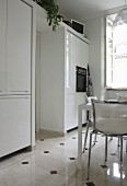 White fitted cupboards and dining set on tiled floor with dark accent tiles