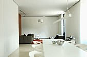 White, modern dining area and lounge area with white arc lamp in open-plan, minimalist interior