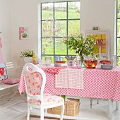 Spring bouquet on table with patterned tablecloth and place mats and vintage chair with country-house-style upholstery