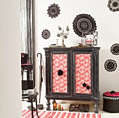 Make-over - vintage cabinet with fabric-covered, ethnic-style doors against wall decorated with black crocheted doilies