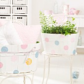 Wooden boxes painted with polka dots on delicate, metal garden chairs